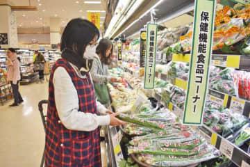 保健機能食品コーナーで県産のニラを手に取る買い物客=14日午前、宮崎市・イオンスタイル宮崎店