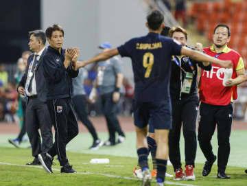 イラクと引き分け準々決勝進出を決め、選手を迎えるタイ代表の西野監督(左手前)=バンコク(共同)