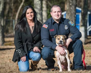 Carol Skaziak, founder of Throw Away Dogs Project, and Firefighter Tyler Van Leer pose for a photo with Hansel. (Courtesy of Carol Ska/)