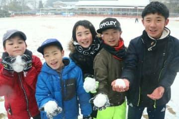 雪玉を手に楽しむ子どもたち=14日午後、竹田市久住町