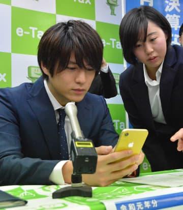 スマートフォンで確定申告書の作成を体験する永田薫さん(左)=岐阜市美江寺町、岐阜北青色会館