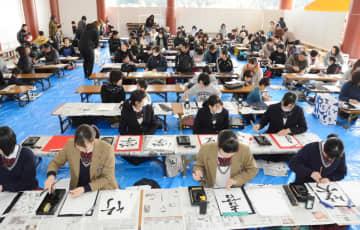 一斉に筆を走らせる書き初め大会の参加者たち=神埼市の王仁博士顕彰公園