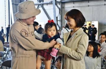 中東派遣を前にわが子を抱く海上自衛隊員=11日、海上自衛隊那覇基地
