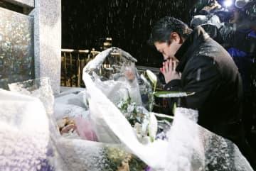 雪の中、スキーバス転落事故現場付近に立つ「祈りの碑」に向かって手を合わせる男性=15日午前0時48分、長野県軽井沢町