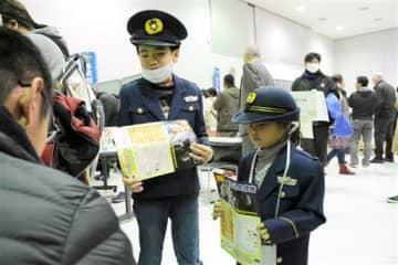 警察官の制服を着て、会場で聞き込みをする子どもたち=八代市
