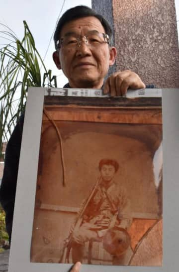 曽祖父・傳治さんの写真を持つ富岡英一さん