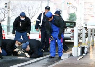 福山市西町2丁目の事故現場を調べる福山東署員たち(15日午前8時37分)