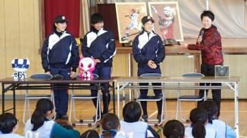 日立の後輩3選手を笑顔で紹介する元ソフトボール日本代表の西山さん(右端)=11日、横須賀市立野比中学校