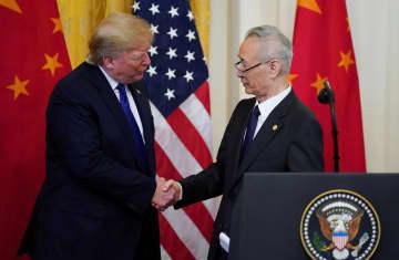 合意文書に署名し握手するトランプ大統領(左)と中国の劉鶴副首相=ワシントン(ロイター=共同)