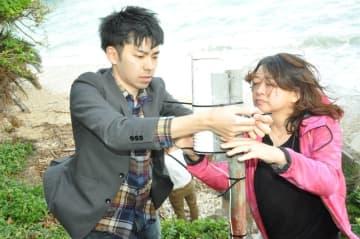 定点観測カメラを設置するメンバーら=8日、浦添市港川