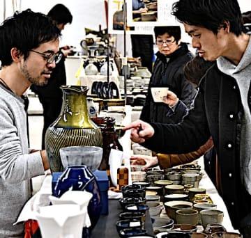 窯元(左)と会話をしながら作品を選ぶ来場者=15日、米子市西福原2丁目の米子天満屋