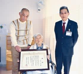 100歳の誕生日を祝福された山口ミヲさん。左は康則さん、右は塩越部長