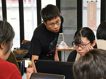 プログラミングに取り組む講座参加者にアドバイスする草刈さん(中央)