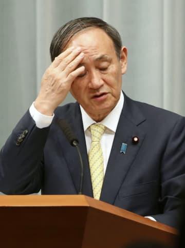 記者会見中、頭に手をやる菅官房長官=16日午前、首相官邸