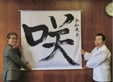 真砂充敏市長(左)に「咲」の掛け軸を寄贈する九鬼家隆宮司=和歌山県田辺市新屋敷町で