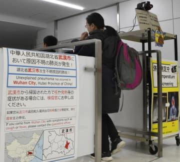 新型のウイルス性肺炎について注意喚起するポスターが掲示された成田空港検疫所を通過する中国湖北省武漢市からの到着客=16日午後