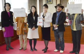 NPO法人ライトハウスの藤原志帆子理事(中央左)から署名を受け取る森法相(同右)=16日、法務省
