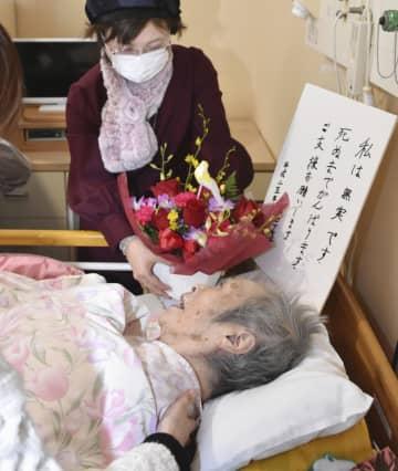 弁護団らから新年のあいさつを受けた原口アヤ子さん(下)=16日午後、鹿児島県内