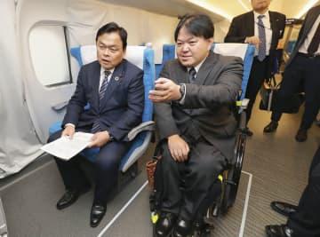 東海道新幹線の新型車両に試乗し、DPI日本会議事務局長で車いす利用者の佐藤聡氏(右)の話を聞く赤羽国交相=16日(画像の一部をモザイク加工しています)