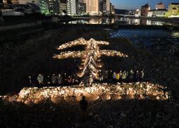 石を「生(せい)」の形に積んだオブジェがライトアップされた=16日午後5時46分、宝塚市湯本町(写真・中西幸大)