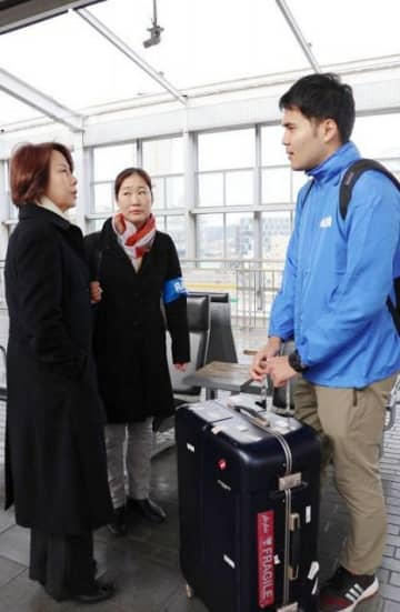 出発前にAMDAスタッフと話す神倉さん(右)=JR岡山駅