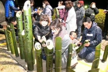 竹灯籠にメッセージを書き入れる住民ら。右端は北山さん=8日、倉敷市真備町箭田