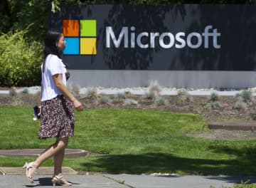 A pedestrian walks a sign on Microsoft Headquarters campus July 17, 2014 in Redmond, Wash. - Stephen Brashear/Getty Images North America/TNS
