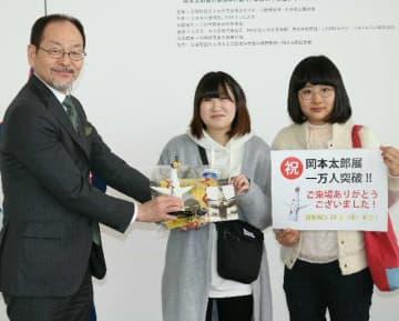 1万人目となり、井上洋一特別顧問(左)から記念品を受け取る辻山舞さん(中央)と宍戸茜さん