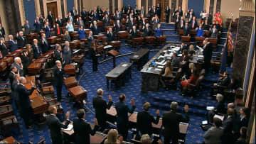 上院本会議場で、宣誓手続きを行うロバーツ最高裁長官と、陪審員役の上院議員=16日、ワシントン(上院提供・AP=共同)