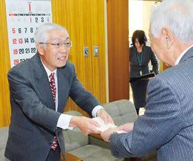 南理事長に善意を手渡す垣内さん(左)