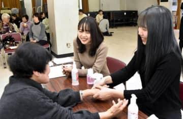 大洲市の被災者らと会話を楽しみながら、ハンドエステを施す学生