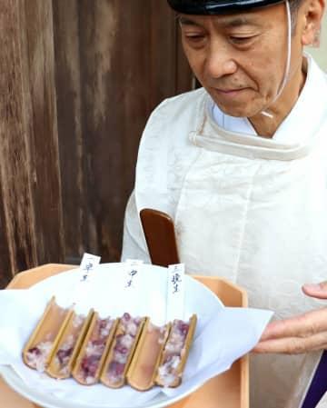竹筒の中の米と小豆の詰まり具合を見る岩田宮司(京都府亀岡市千歳町・出雲大神宮)