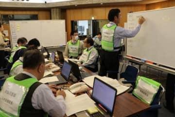 人的、物的支援の割り振りなどの対応を確認する職員=岡山県庁