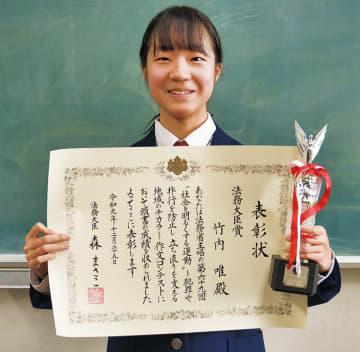 賞状とトロフィーを手にする竹内さん
