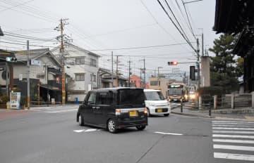 太秦交差点内に引かれた誘導線(中央)に沿って右折する乗用車=京都市右京区