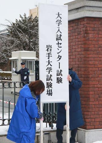 正門前に大学入試センター試験岩手大試験場を示す看板を設置する職員