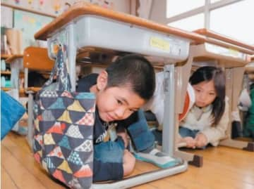 大分県内の学校では地震や津波を想定した避難訓練を実施。机の下に身を隠す児童=17日、大分市の日岡小