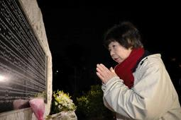 両親の名前が刻まれた碑の前で、手を合わせる原田美智子さん=17日午前6時31分、西宮市奥畑(撮影・吉田敦史)