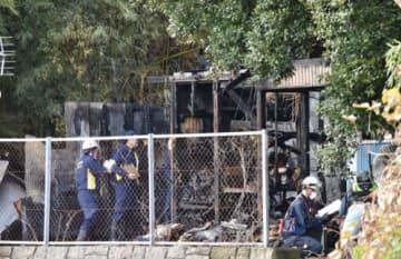 火災現場を調べる県警の捜査員ら=横須賀市汐入町5丁目