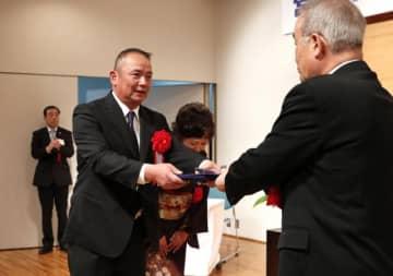 複合経営で表彰を受ける鬼塚晃さん(左)と妻の里美さん=17日午前、宮日会館