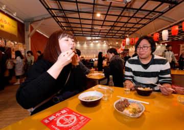 鍋の食べ比べを楽しむ女性=横浜赤レンガ倉庫の特設テント