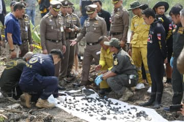 Over 200 human bone fragments are found on Friday in a new search of the pond are placed on a white sheet for inspection at a house owned by murder suspect Apichai Ongwisit, 40, in Bang Khae district. (Photos by Pornprom Satrabhaya)