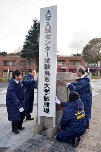 正門前に看板を設置する職員=17日、鳥取市の鳥取大