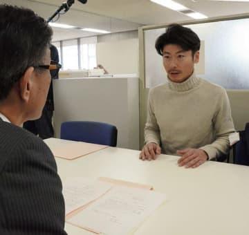 市役所本庁舎建て替えに関する公開質問状を提出する市民団体「庁舎建て替えを考える会」の西川文武代表(右)=熊本市役所