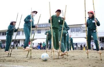 宮城県丸森町立金山小で開かれた竹馬運動会で、サッカーをする児童=18日午前