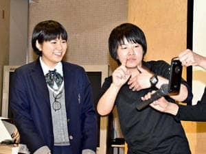 遠隔手話通訳サービスを実演する山中事務局長(右)