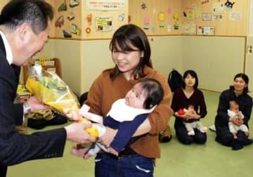 てくるんの利用者100万人達成を祝い、松山市の野志市長(左)から花束を受け取る親子