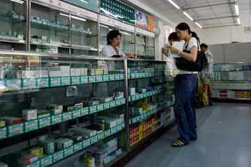 Chinese customers buy medicines at a pharmacy in Beijing. (Reuters Photo)