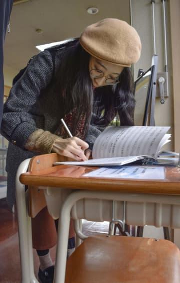 「響け!ユーフォニアム」の舞台、京都府宇治市を訪れノートに書き込む女性=18日