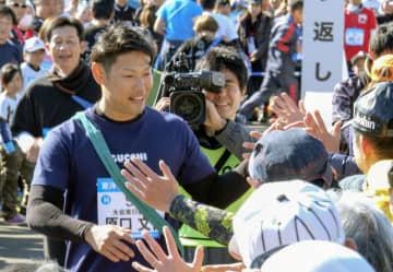 チャリティーのリレーマラソンで沿道のファンとタッチを交わす阪神タイガースの原口文仁選手=18日、和歌山県すさみ町